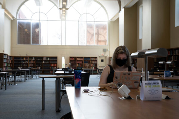A UNC student studies in Davis Library amidst signage reminding visitors to wear a mask and maintain social distancing. (photo by Elise Mahon)