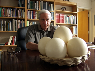Alan Feduccia with ostrich eggs on his desk. Photo by Jason Smith of UNC Endeavors.