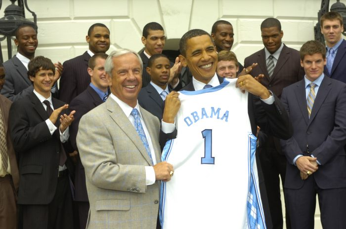 Roy Williams presenting President Barack Obama a Carolina jersey with the number 1 and the name Obama.