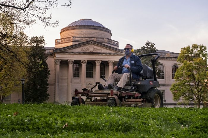 """Eric Tolar cuts grass on Polk Place in front of Wilson Library. When few people were on campus from March into summer, Tolar and his crewmates took care of 81 acres of the University's most visible outdoor areas. """"The number one thing we've been about is being safe,"""" Tolar said. """"I've felt fortunate to be at work at times when the news is 24-7 and can bring you down. We were outside and able to take our minds off of it. And, we could see that people were here at times."""""""