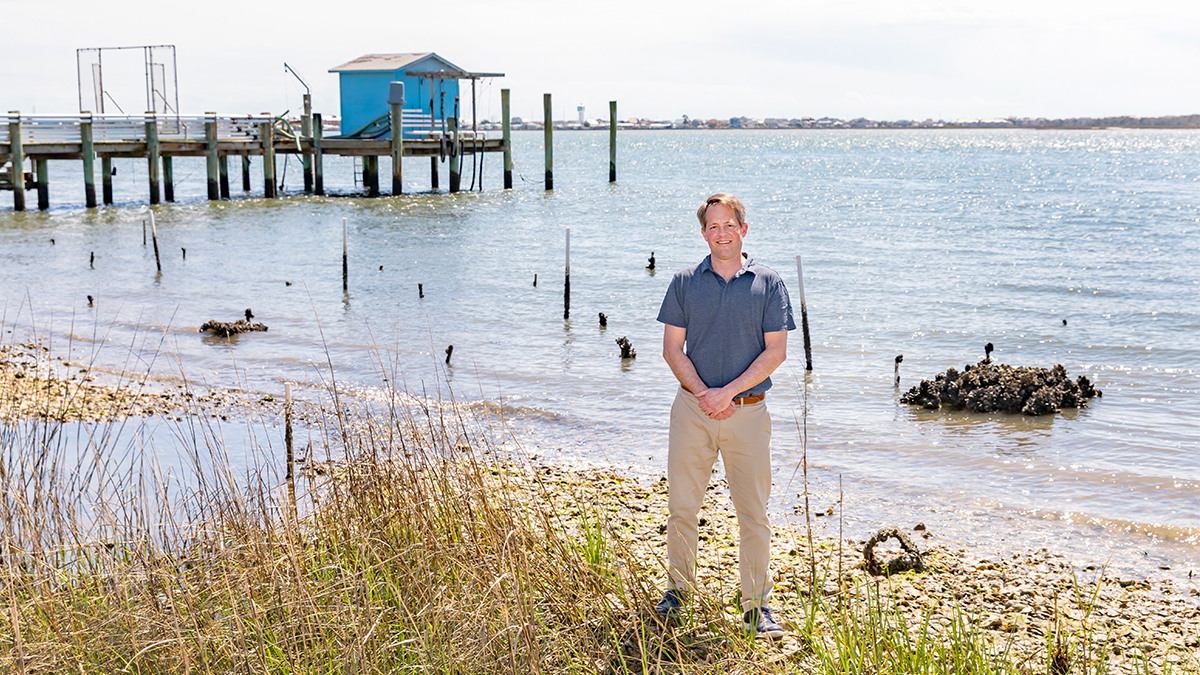 """Professor Michael Piehler stands at the site of a shoreline restoration project on March 30, 2021, at the Institute of Marine Sciences in Morehead City. Piehler is working with professor Antonio Rodriguez and associate professor Joel Fodrie on the project with the goal of implementing a new carbon offset for UNC through the creation of a saltmarsh and oyster-reef habitat near the IMS shorefront. They indicate that saltmarshes are """"blue carbon"""" habitats which fix carbon dioxide in excess of respiration and bury carbon in sediments. The oyster-reef acts as a barrier, protecting the saltmarsh from waves and currents. Team leaders said their hope is for the project to serve as an enduring educational tool and demonstration of UNC's broad vision in the ongoing efforts to achieve carbon neutrality. The IMS is an off-campus research laboratory, teaching, outreach, and service unit of the University of North Carolina at Chapel Hill. (Johnny Andrews/UNC-Chapel Hill)"""