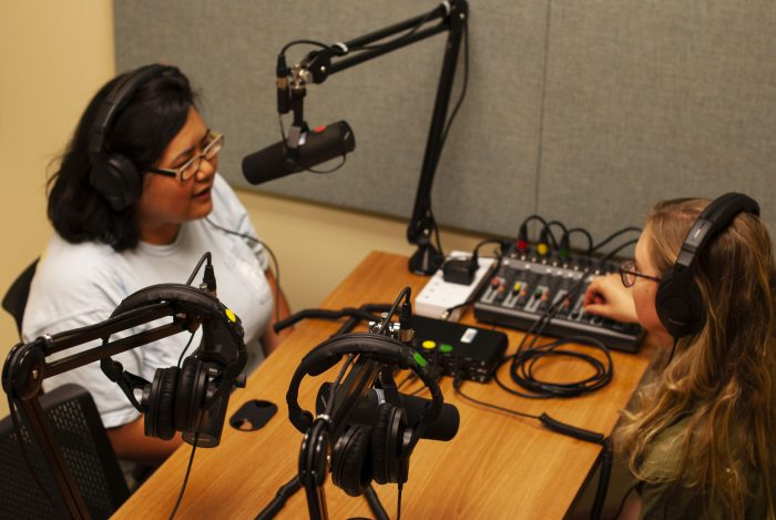 Two women at desk, one speaking into overhead microphone, in podcast studio.