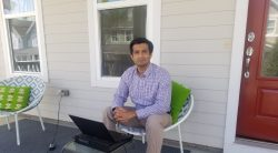 Man sitting on porch working on a laptop