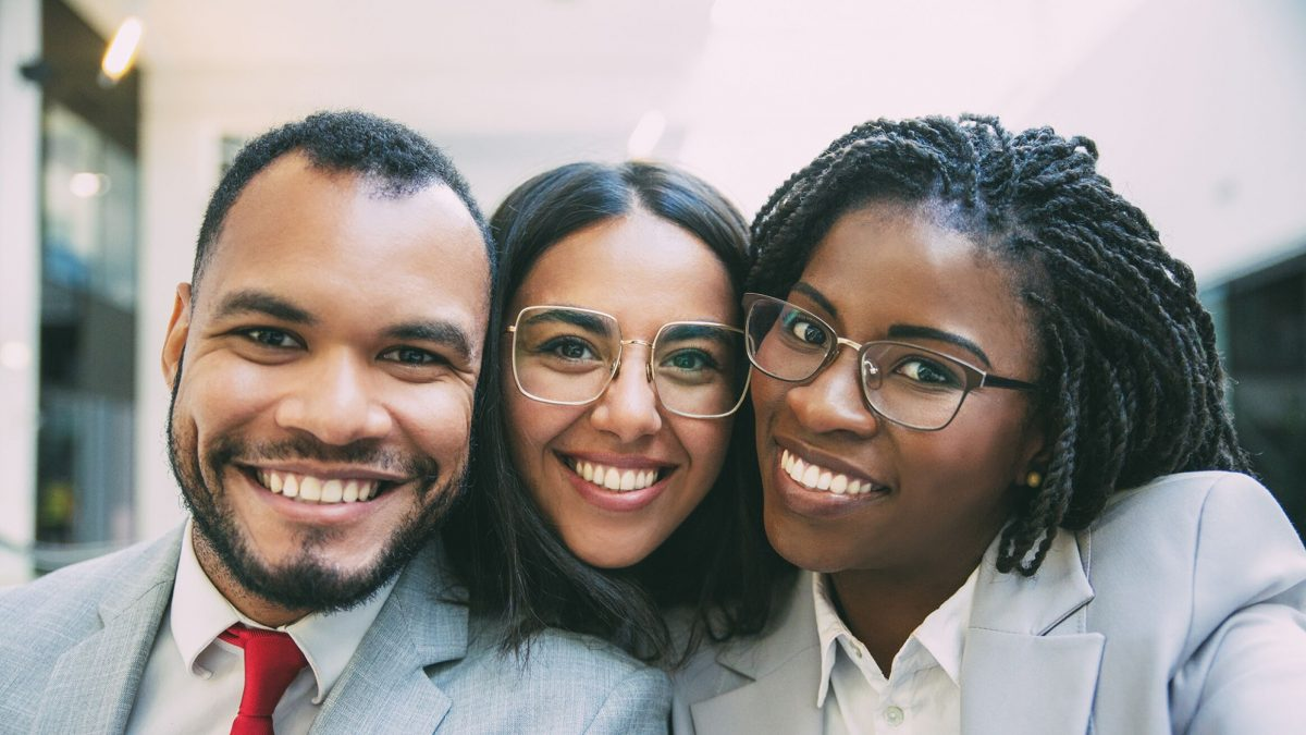 three young people of color in business suits