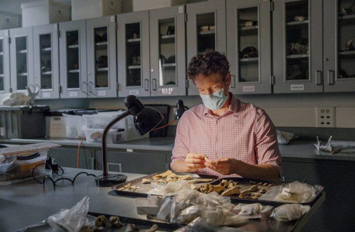 Ben Arbuckle, associate professor of anthropology, examines animal remains. (Photo: Jeyhoun Allebaugh)