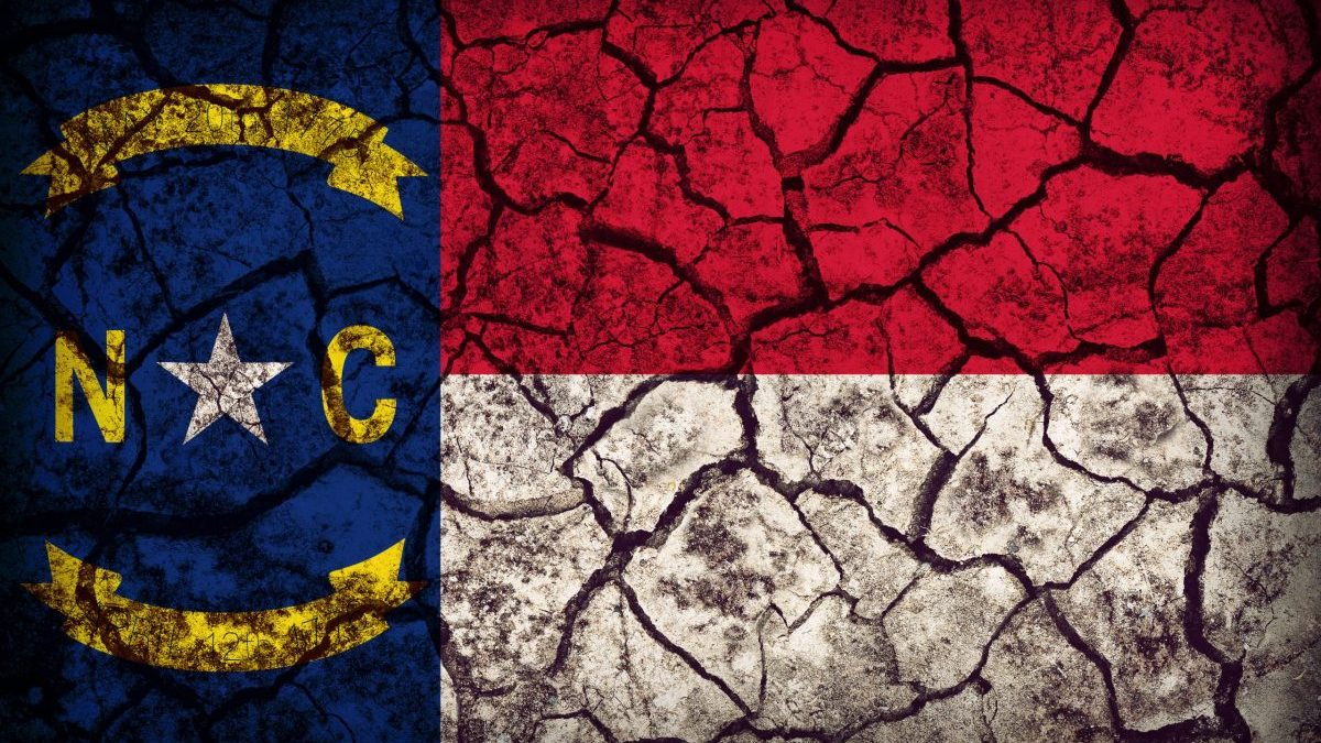 North Carolina flag superimposed over image of cracked , dry soil.