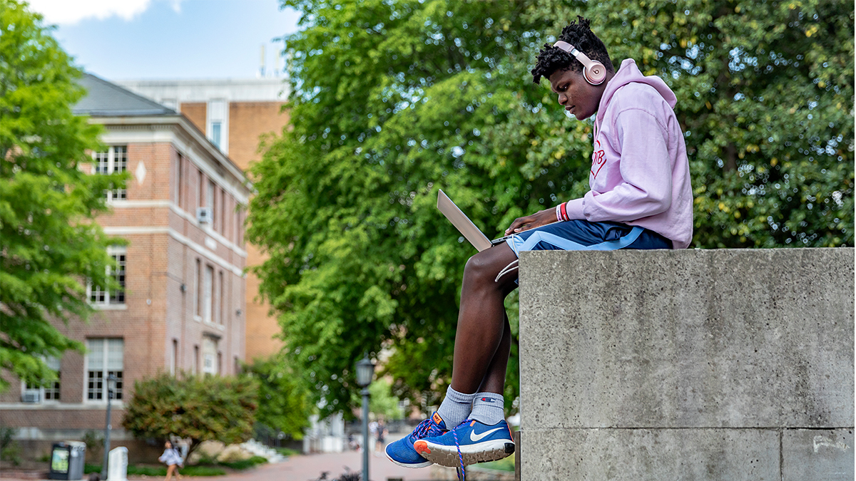 UNC senior Jaylin Pierce sits near the steps of Wilson Library overlooking Polk Place. According to the University's COVID-19 Community Standards, masks aren't required outside. (Johnny Andrews/UNC-Chapel Hill)