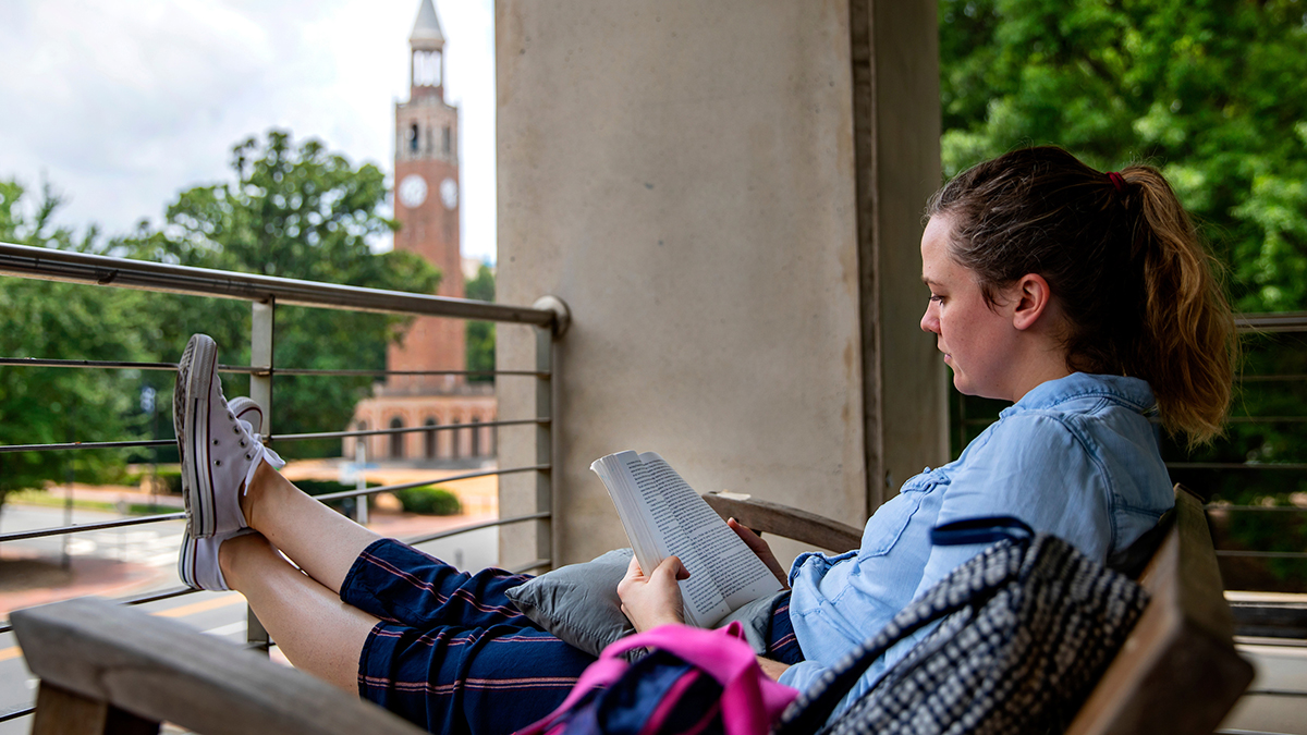 Woman sitting on balcony of Student Stores.