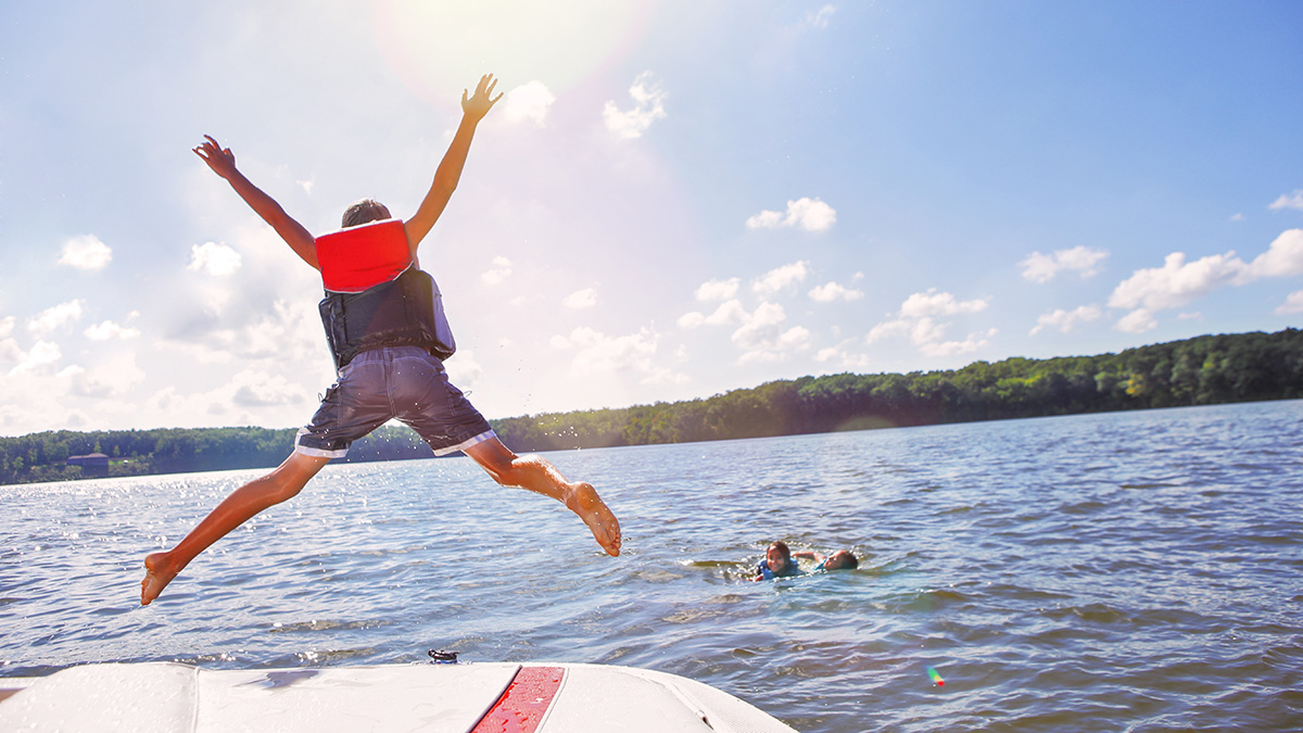 Boy jumping from a boat into a lake. He's wearing a life vest.
