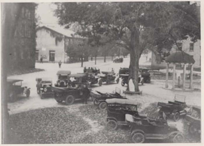 Old Well in 1920s or 1930s with jalopies parked all around it.