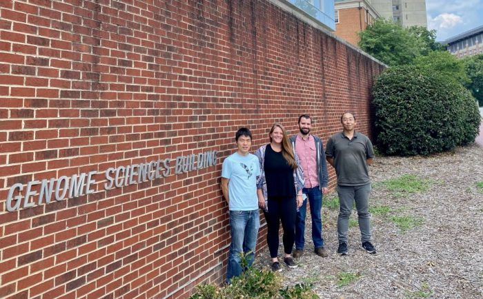 four people outside Genome Sciences building