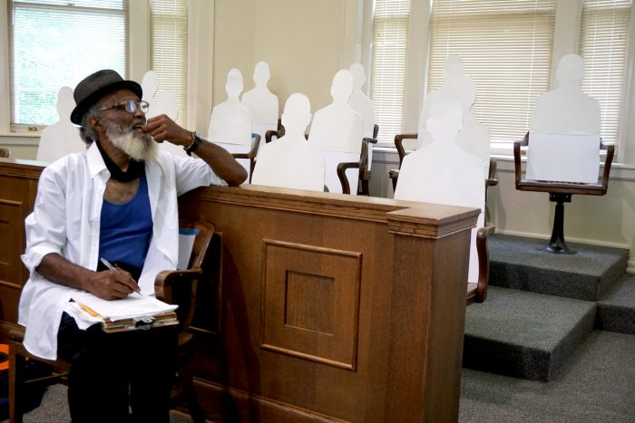 Playwright Thomas Park listens to a rehearsal while sitting in front of cut-outs representing an all-white jury.