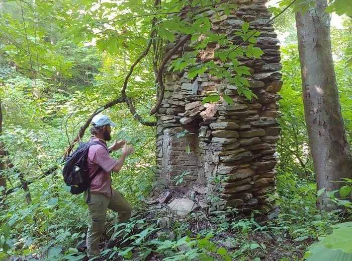 man in front of abandoned rock chimney in forest