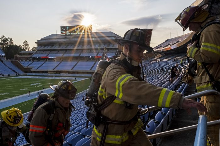 The run rises over Kenan Stadium as four firefighters in full gear climb stairs.