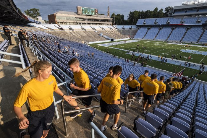 Navy ROTC cadets in black shorts and yellow T-shirts climb stairs in Kenan Stadium.