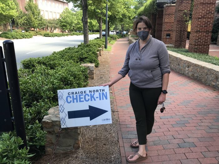 Woman in mask stands beside a sign that reads: Craige North check-in
