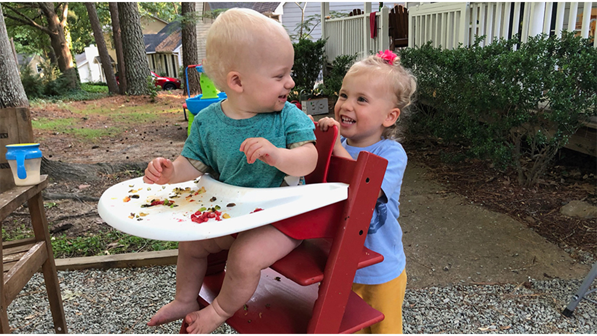Two children, one in a high chair