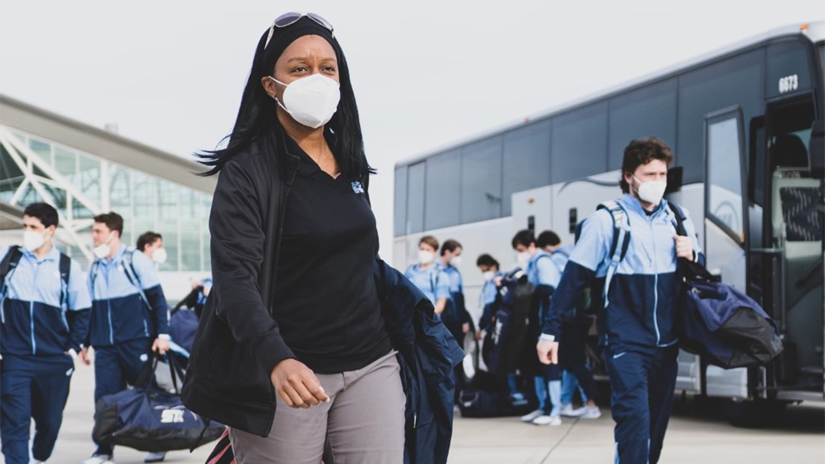 Woman in mask carrying gear bag in a locker room with athletes who also wear masks.