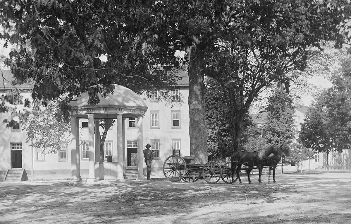 Black man with horse drawn wagon standing next to Old Well on UNC campus, May 1, 1902, 3:20 pm; P0013/0269, in the Collier Cobb Photographic Collection (P0013), North Carolina Collection Photographic Archives, The Wilson Library, University of North Carolina at Chapel Hill.