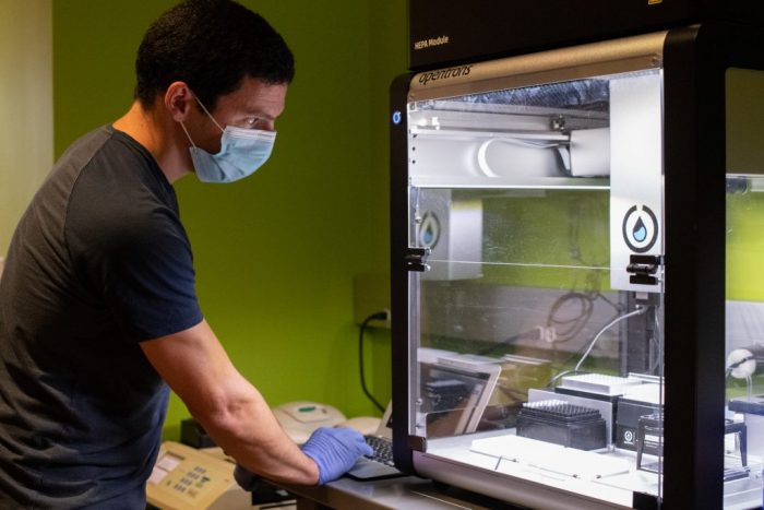 Jeremy Wang operates the Opentrons OT-2 robot, purchased with gifts to the UNC COVID-19 Research Accelerator Fund.