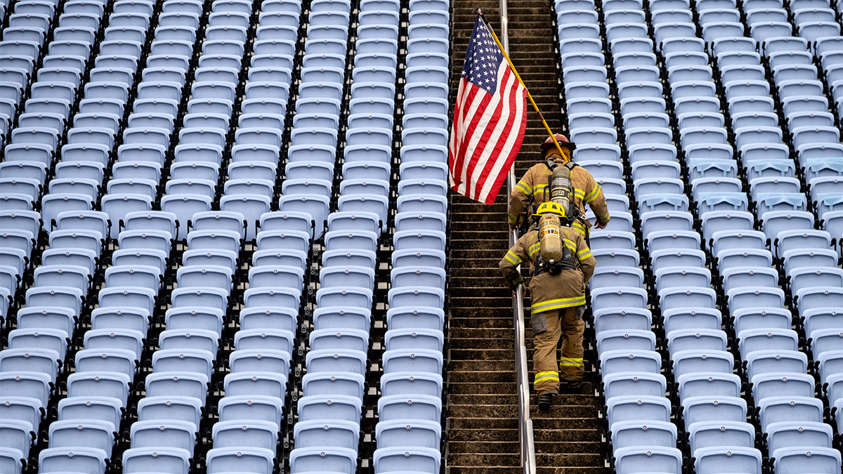 Two firefighters in full gear and carrying a flag climb the steps of Kenan Stadium between empty seats.
