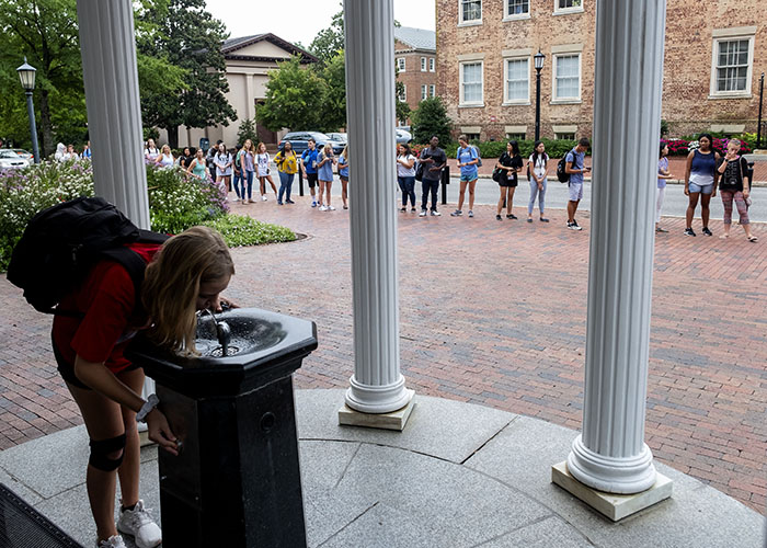 Students in 2018 line up for a sip from the Old Well.