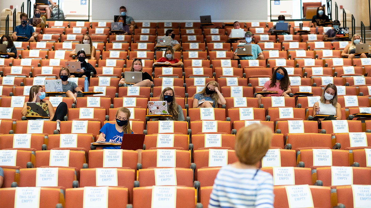 Sparsely filled lecture hall with signs on the seats requiring COVID-19 spacing and students wearing masks.