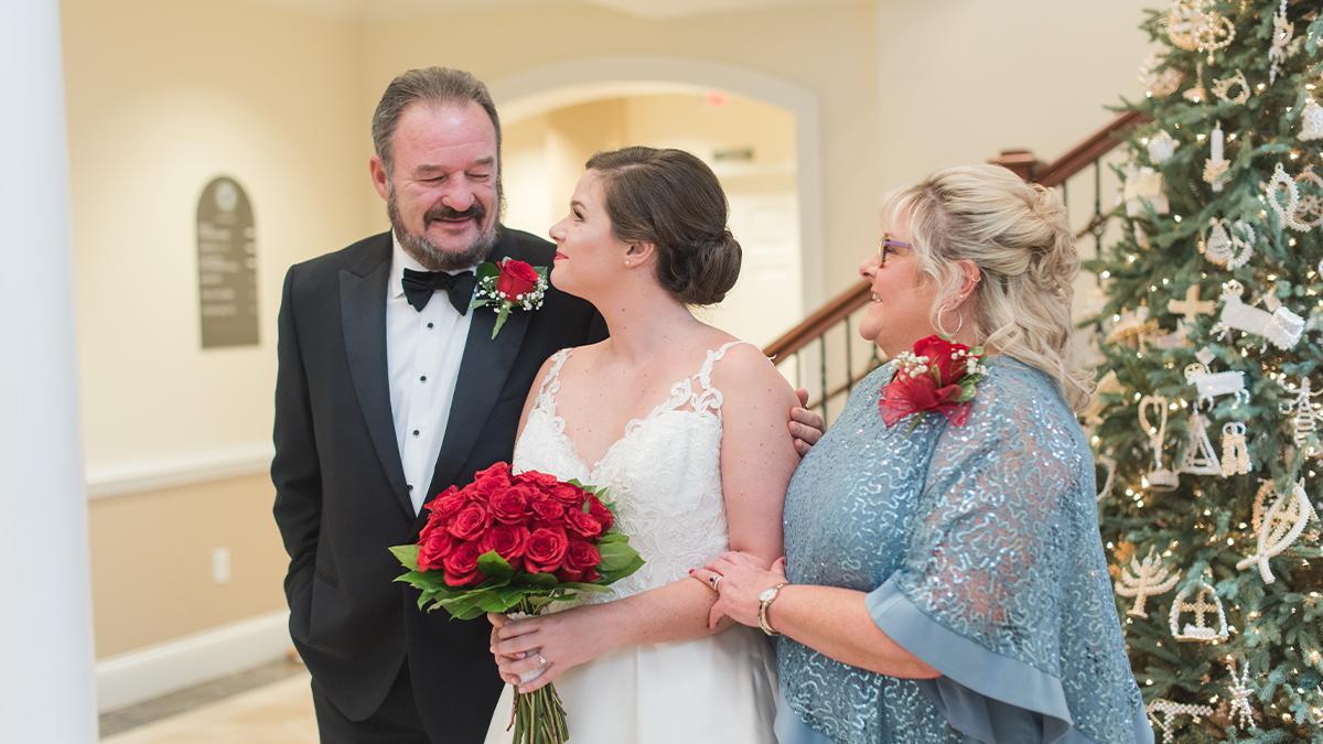 A father and mother in formal attire flank their daughter, who wears a white wedding dress and holds a bouquet of roses.
